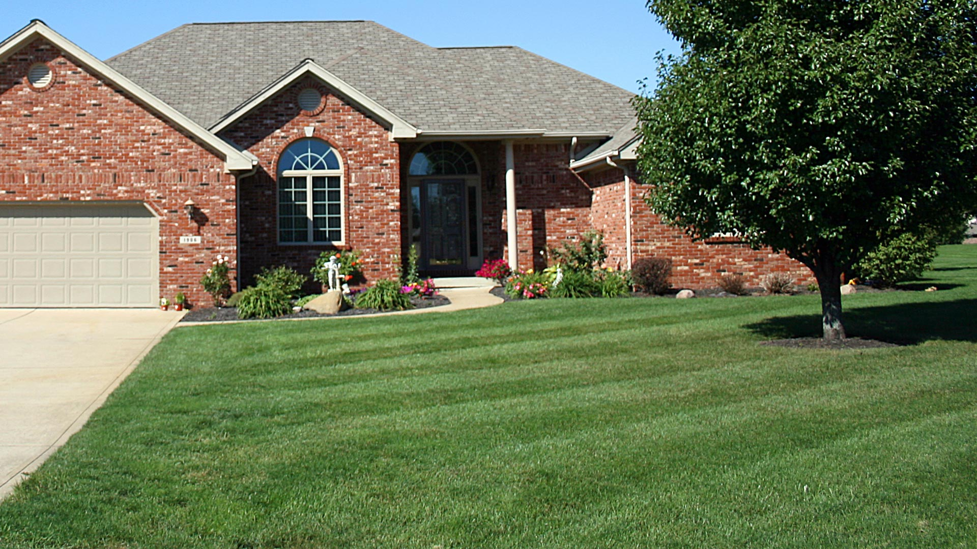 A professionally maintained lawn and landscape at a home in Des Moines, IA.