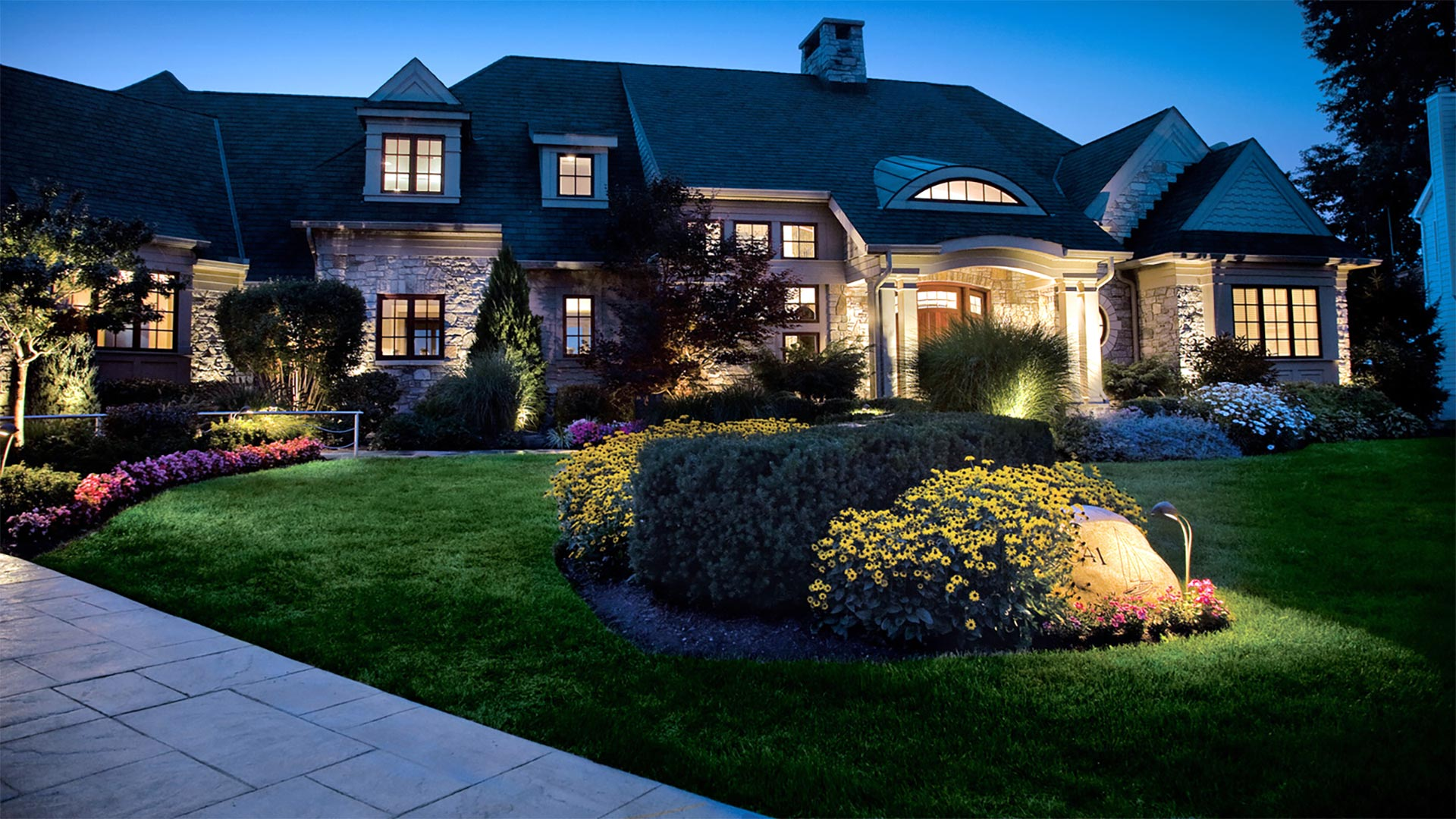 A home with outdoor lighting and landscaping in Adel, IA.