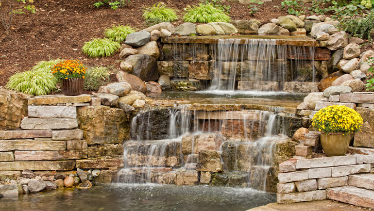 Stacked stone hardscape waterfall for homeowner in Des Moines, IA.