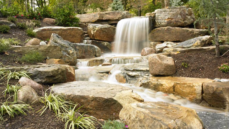 A beautiful rock waterfall professionally installed by our skilled employees at a home in West Des Moines, IA.