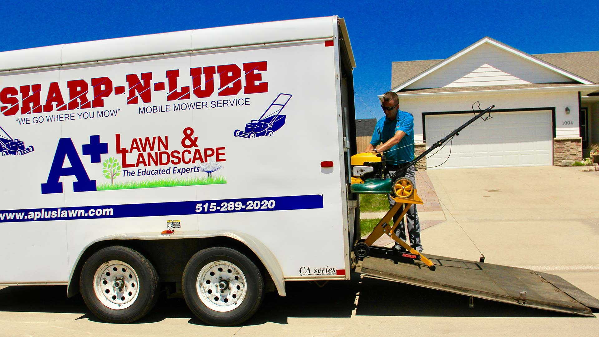 Our sharp-n-lube trailer open with a landscaper at work in front of a home in Des Moines. IA.