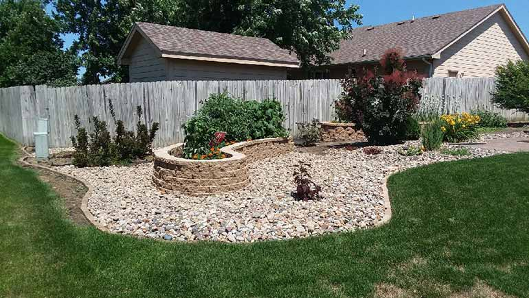 Custom stone landscaping and retaining wall in Bondurant, IA.