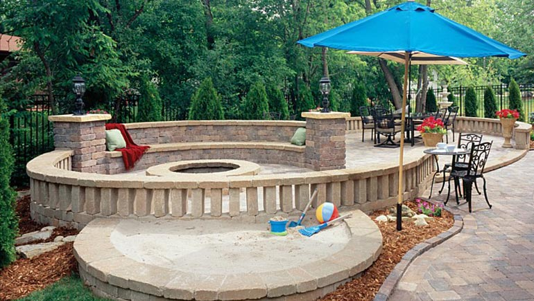 Custom built patio, seating wall, fire pit and landscaping at a home in Polk City, Iowa.