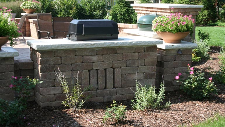 Patio, seating wall, built-in grill, and new landscaping at a home in Pleasant Hill, Iowa.