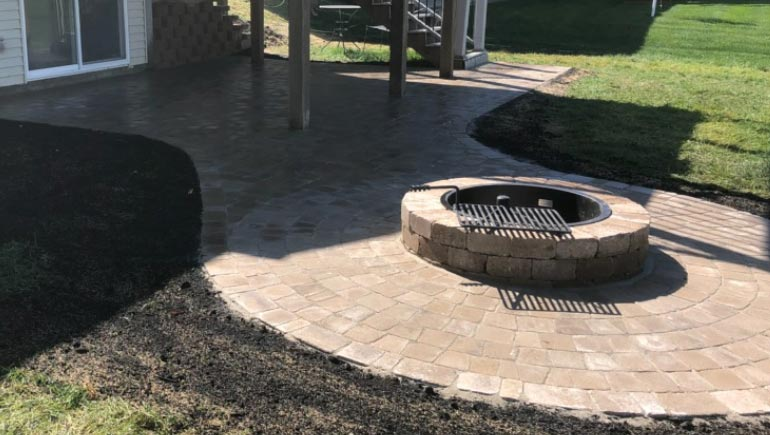 Custom fire pit and paver patio at a property in West Des Moines, Iowa.