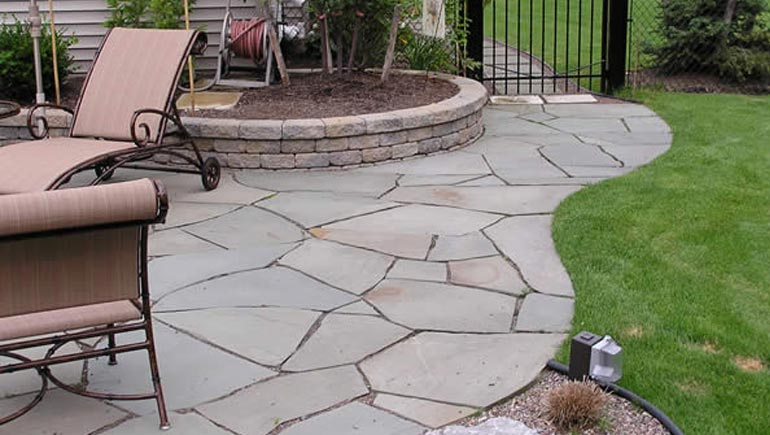 A new flagstone patio and pathway designed and installed by our team at a home in West Des Moines, IA