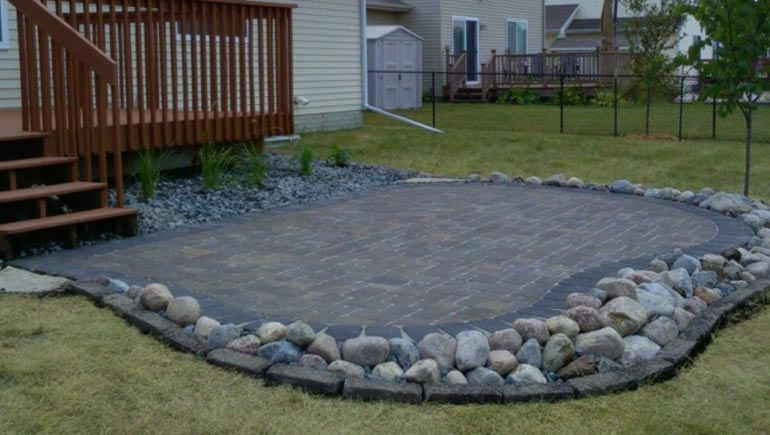 Hardscape paver patio with rock border at a home in Waukee, Iowa.