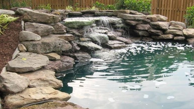 Water feature with a pond and a waterfall at a home in Des Moines, IA.