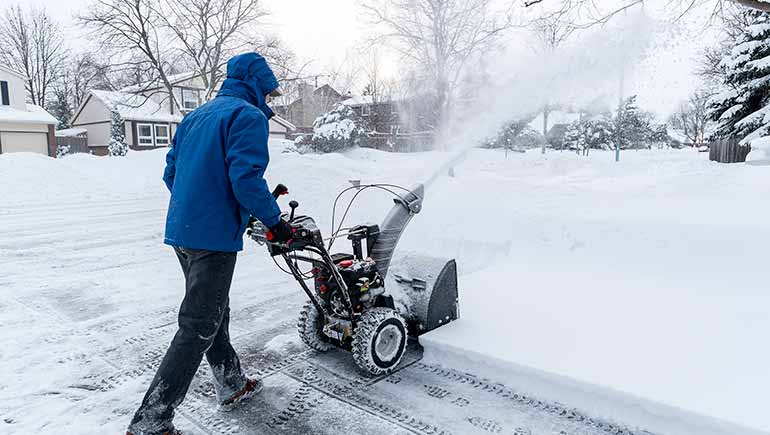 Lawn care worker using a snow blowing machine in Ankeny, IA.