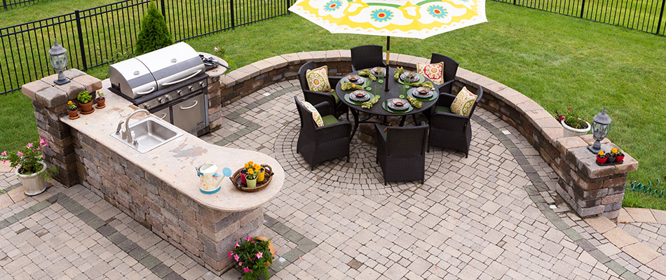 A bird's eye view of an outdoor kitchen and paved patio landscape.