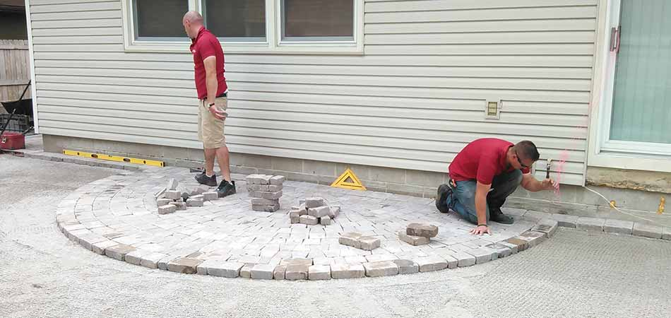Team members from A+ Lawn & Landscape are building a paver patio for a homeowner in Des Moines.