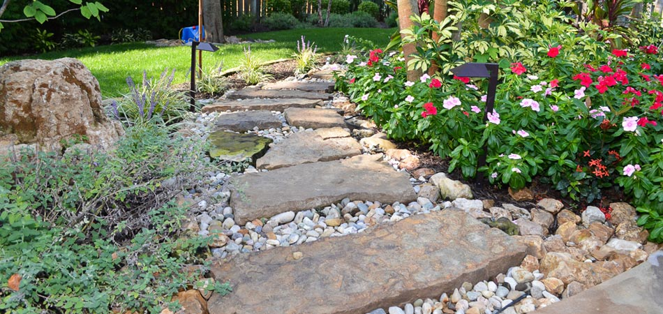 Recently installed hardscape pathway and new landscaping at a residential property in Urbandale, IA.