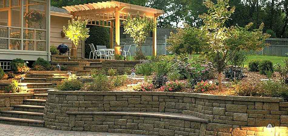 The stone hardscaping of this home in Des Moines is being highlighted by well placed outdoor lighting.