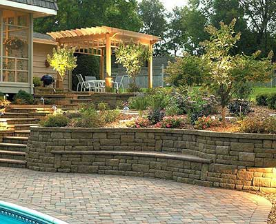 Outdoor living area with custom landscape lighting and retaining wall in Ankeny, IA.