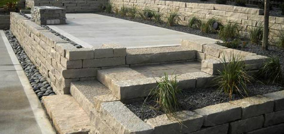 A recently constructed retaining wall with planters and rock surround at a home in Clive, Iowa.