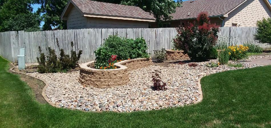 New rock mulch around a newly built hardscape feature with plantings.
