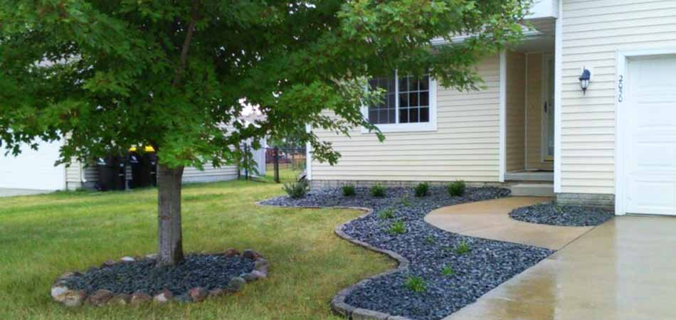 Rocks that have been placed at the base of a tree in the front yard of a Ankeny homeowner.