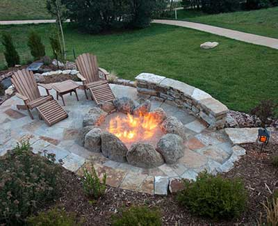 Custom flagstone seating wall and fire pit patio in Des Moines, IA.