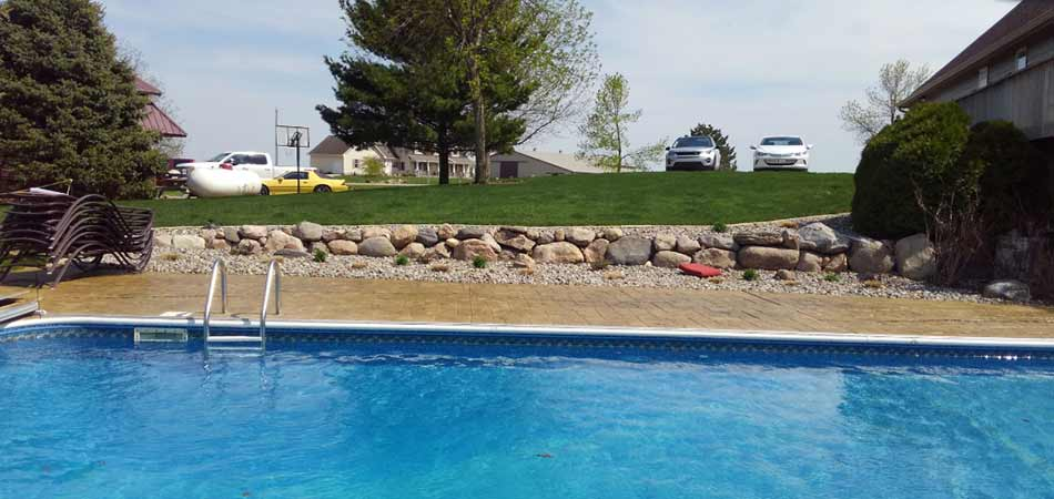 This stonewall was built for a Des Moines homeowner, as a natural looking accent for the pool in the foregrounde.