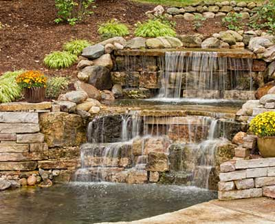 Custom stone waterfall and pond installation in West Des Moines, IA.