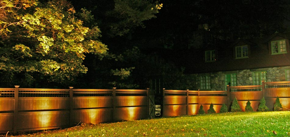 Outdoor lighting with up-lighting technique used on a privacy fence at a home in Ankeny, IA.